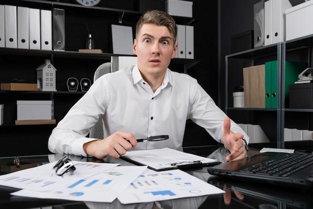 Молодой человек с лупой и страховкой сидит за столом в ярком офисе