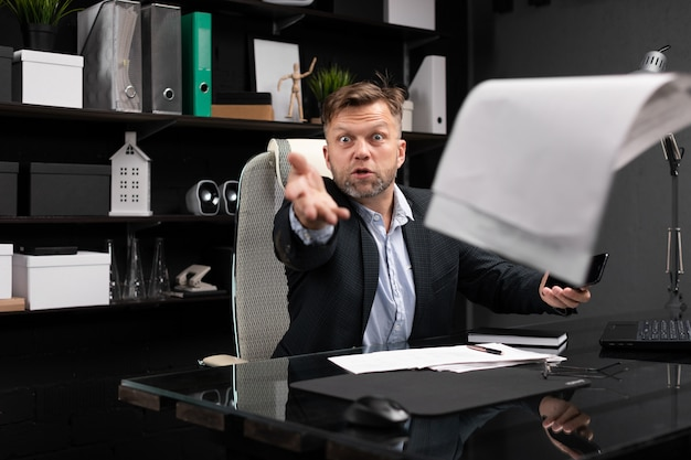 Разъяренный бизнесмен бросает документы в офис