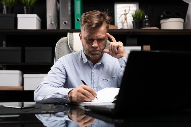 Молодой человек сидит за компьютерным столом и делает записи в дневнике