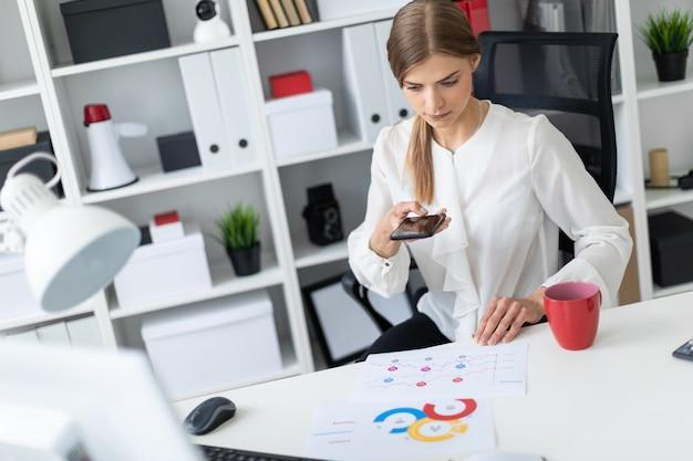 Молодая девушка сидит за столом в офисе и делает фотографии на телефон.