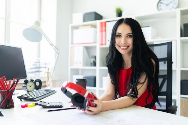 Красивая молодая девушка с наушниками в руках сидит в офисе за столом.