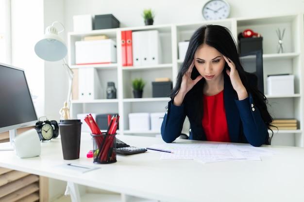 Красивая молодая девушка сидит в кабинете за столом и держит руки за голову.