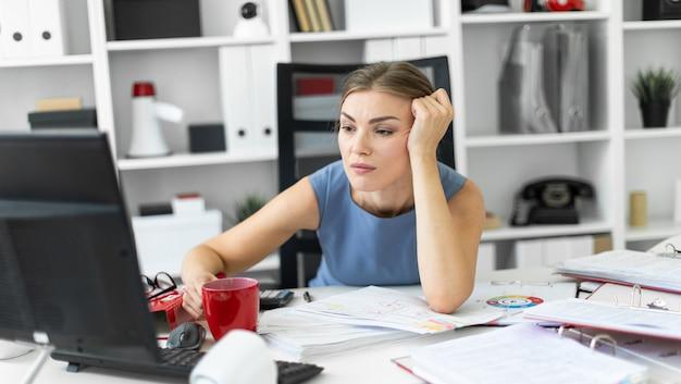 Молодая девушка сидит в офисе за компьютерным столом и подпирает руку на голову.