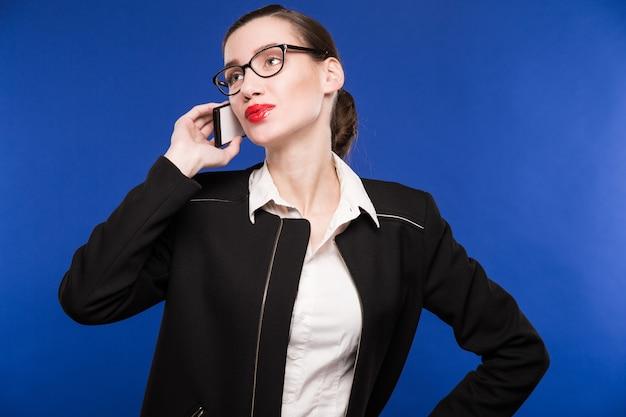 電話で話しているメガネの若い女性