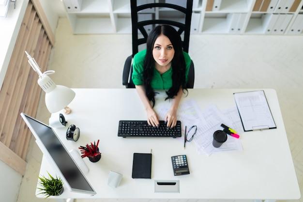 Взгляд сверху маленькой девочки сидя на столе офиса и печатая на клавиатуре.
