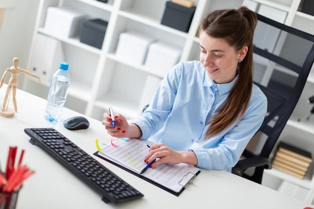 Молодая девушка сидит за столом в офисе и держит маркер в руке.