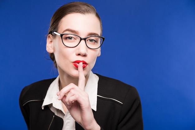 顔の近くの手でメガネのブルネットの少女の肖像画