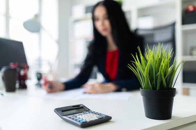 Калькулятор лежит на столе в офисе. красивая маленькая девочка работая с калькулятором и документами в офисе на таблице.