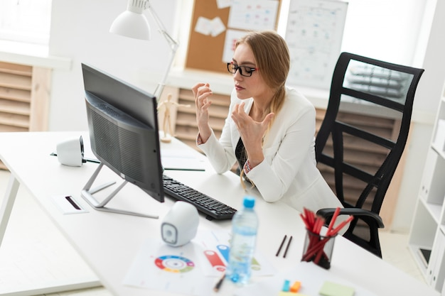若い女の子がオフィスのテーブルに座って、モニターを見て指を曲げています。