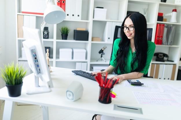 Молодая девушка в очках работает в офисе с компьютером, калькулятором и документами.