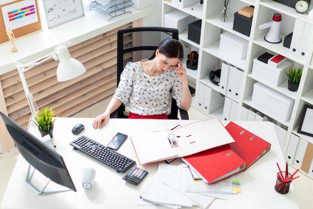 コンピューターテーブルでオフィスの椅子に座っている若い女の子。
