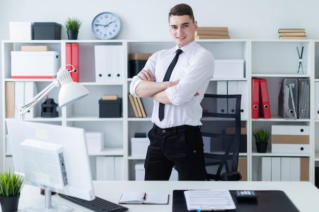 若い男はテーブルの近くのオフィスに立ち、手を胸に当てました。