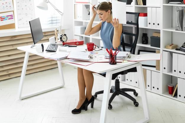 Молодая девушка сидит за столом в офисе и держит в руках документ и ручку.
