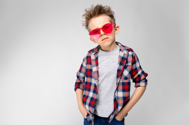格子縞のシャツ、グレーのシャツ、ジーンズでハンサムな男の子