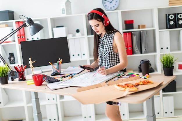若い女の子がテーブルの近くに立って、マーカーと電話を手に持っています。テーブルの上には磁気ボードがあります。
