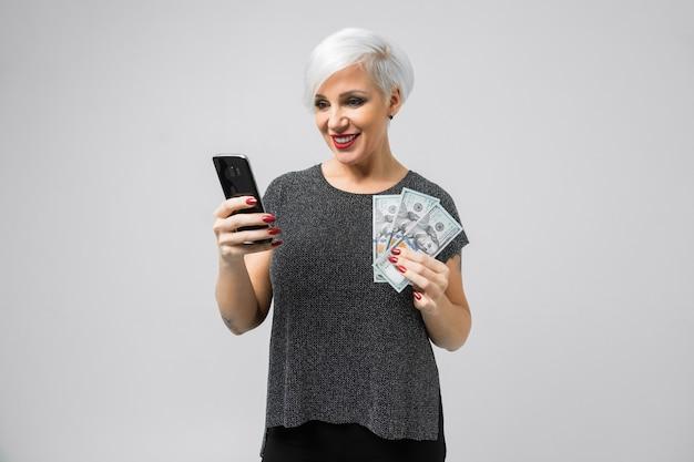 Молодая девушка с телефоном и веером долларов в руках стоит изолированные на свет
