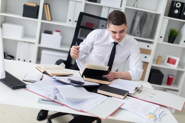 本、ドキュメント、コンピューターとオフィスのテーブルで働く若い男。