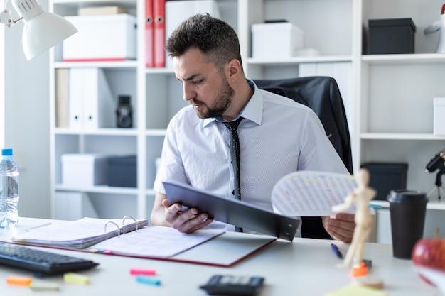 男が事務所に座って文書をスクロールします。