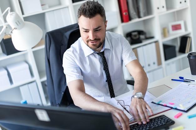 男はオフィスのテーブルに座って文書とコンピューターを操作しています。