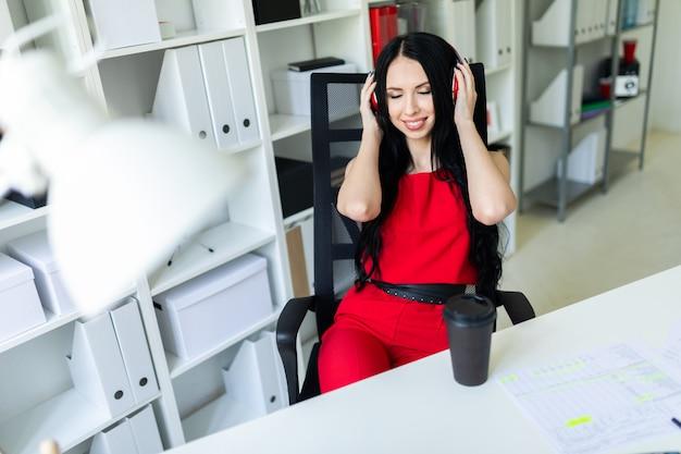Красивая молодая девушка в наушниках сидит в офисе за столом.