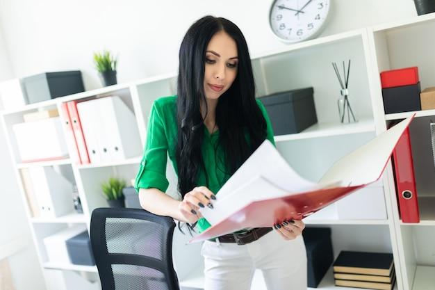 Молодая девушка в офисе держит папку с документами.