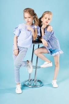 Девушки-близнецы в голубых одеждах позируют возле барного стула на синем.