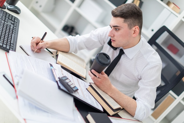 本、ドキュメント、コンピューターとオフィスのテーブルで働く若い男。彼は一杯のコーヒーを持っています。