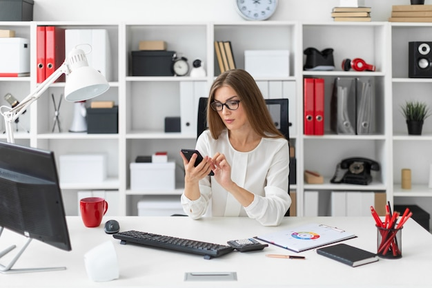 Молодая девушка сидит за столом в офисе и держит телефон.