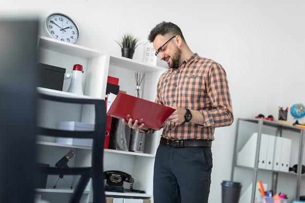 事務所の男が棚の近くに立ち、書類の入ったフォルダーをスクロールします。