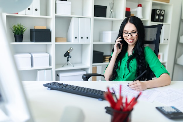 Молодая девушка в очках в офисе говорит по телефону и держит карандаш в руке.
