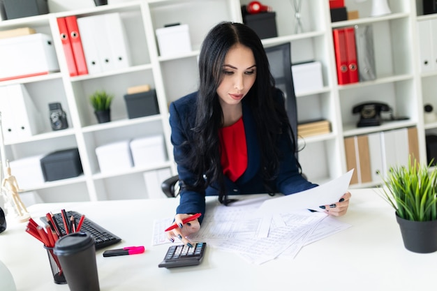 Красивая молодая девушка работает с калькулятором и документами в офисе за столом