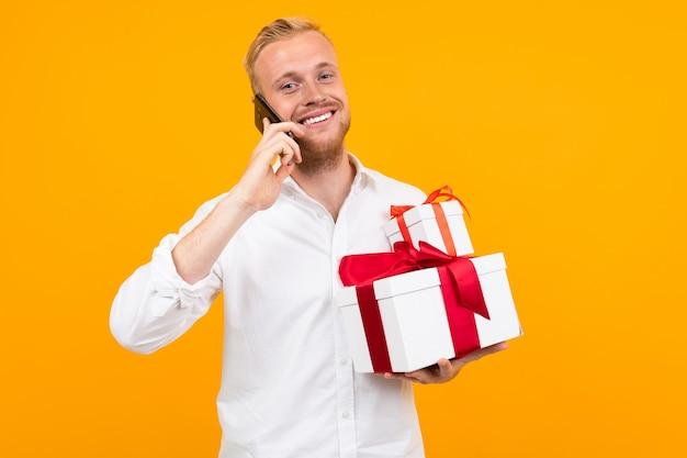 白いシャツにブロンドの髪を持つ若い美しい男ギフトと白いボックスを保持し、黄色に分離された電話をかける