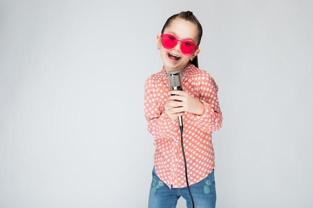 オレンジ色のシャツ、メガネ、ブルージーンズの女の子