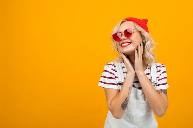 短い金髪の巻き毛と白いオーバーオールで明るいメイクと美しい若い女性。赤いサングラスと赤い帽子のサインと笑顔、オレンジ色の分離の肖像画