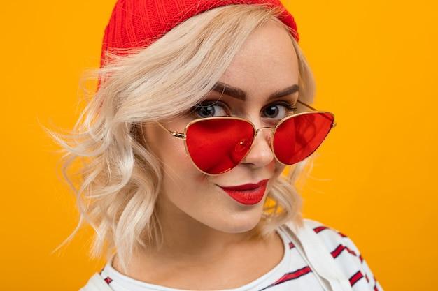 短い金髪の巻き毛と白いオーバーオールで明るいメイクと美しい若い女性の肖像画。赤いサングラスとオレンジに分離された赤い帽子笑顔