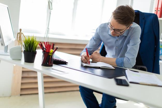 若い男がオフィスのコンピューターの机に座って、ノートに書いています。