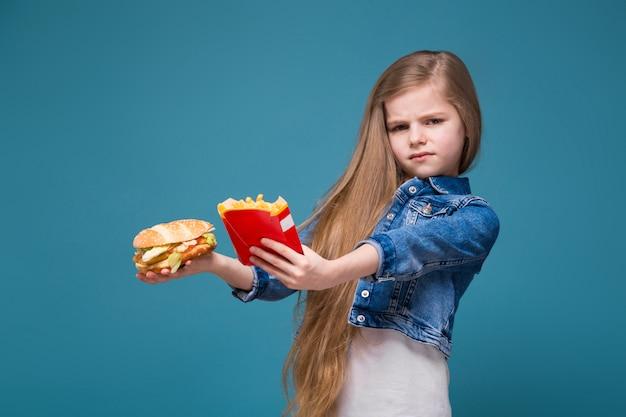 長い茶色の髪とジーンズのジャケットの小さなかわいい女の子はハンバーガーとフライドポテトを保持します。
