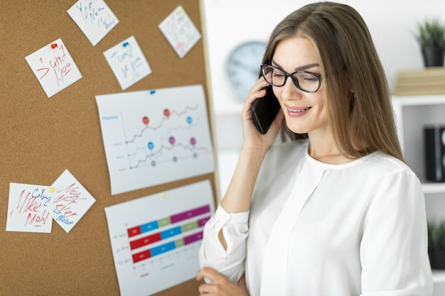 Молодая девушка стоит возле доски с наклейками и разговаривает по телефону.