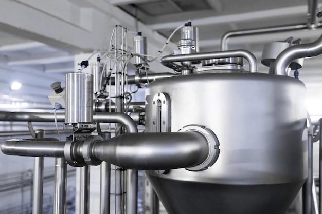 Стальные резервуары или чаны, трубопроводы и другое оборудование в цехе завода