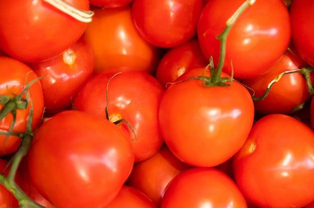 Красная сочная мясистая куча глазированных помидоров крупным планом, овощной, салатный ингредиент