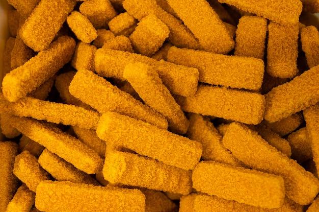 明るいオレンジ色のおいしい魚のスティックの束または伝統的な英国料理の魚の指。クローズアップ、フラットレイ。