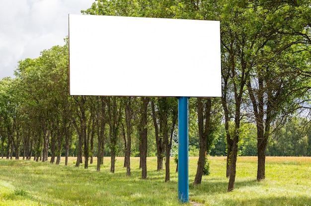 道路に沿ってフィールドに立っている白い空白の広告板のモックアップ