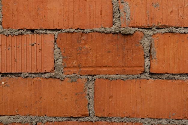 隙間にすり鉢が付いたぼろぼろの赤レンガの壁