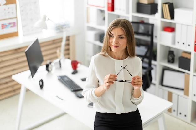 Молодая девушка стоит, опираясь на стол в офисе и держит очки в руке.
