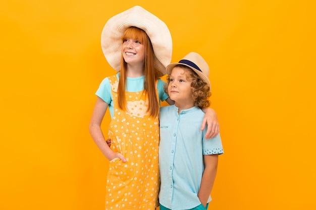 Двое рыжеволосых детей в летних шапочках на разноцветной желтой
