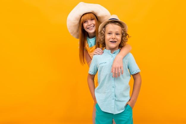 Рыжеволосая девушка выглядывает из-за мальчика в летних шляпах на желтом фоне