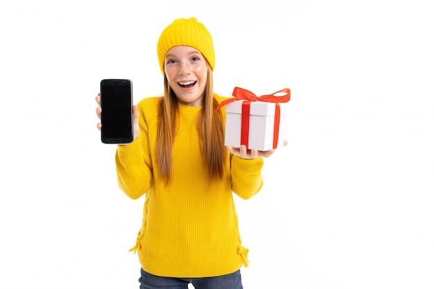 電話と白の手の中の贈り物と幸せの赤い髪の少女