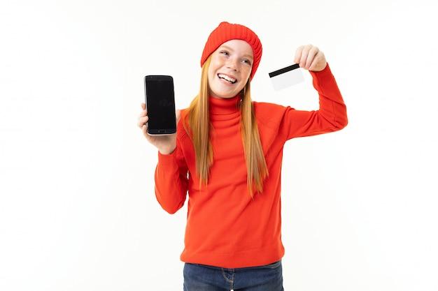 Радостная девушка смотрит, показывает экран телефона и держит кредитную карту на белом