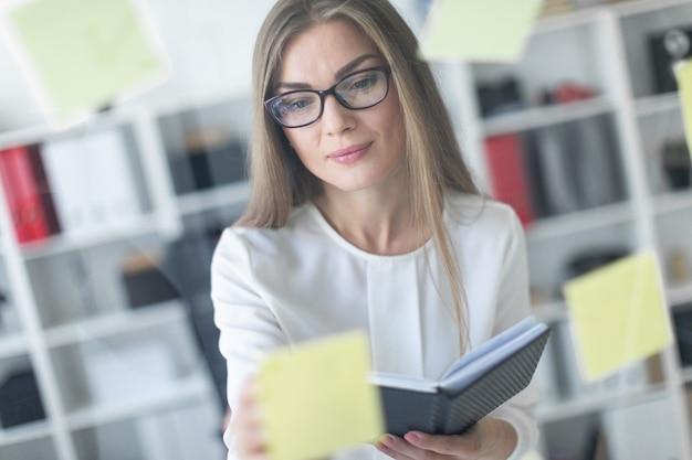 Молодая девушка стоит возле прозрачной доски с наклейками и держит в руках блокнот и ручку.