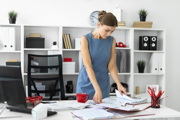 若い女の子がオフィスのテーブルのそばに立ち、書類をスクロールします。
